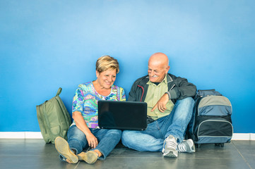 Happy senior couple sitting on floor with laptop and backpack