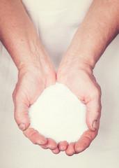 Elderly hands holding rock salt  with vintage style