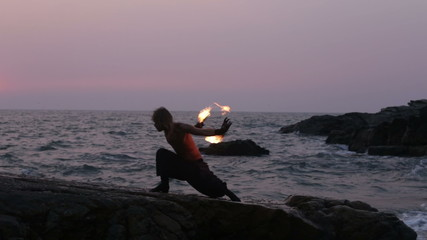 man turns fire poi standing on a cliff near the ocean at sunset
