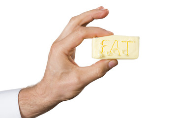 Hand with with a piece of butter.
