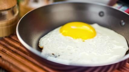 Fried eggs on a wooden table, breakfast