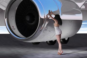 Junge Frau im Vergleich zur Größe eines Flugzeugtriebwerks