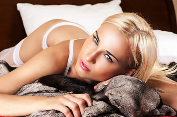 portrait beautiful sexy blond woman lying in furs