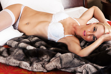 beautiful fashionable blond woman in lingerie lying on a bed