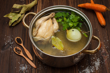 chicken broth with vegetables and spices in a saucepan
