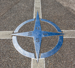 Decorative compass on the cement ground.