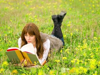 Девушка читает книгу на цветочной поляне