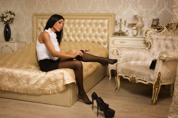 Sensual woman in high heels take off black stockings