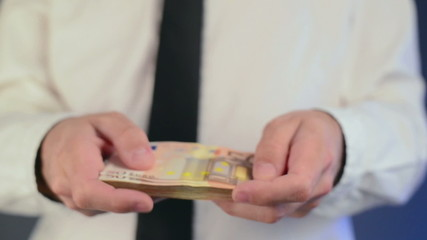 Businessman counting 50 euro banknotes money. Concept of salary