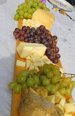 cheese and grapes on the wooden cutting board during a picnic ou
