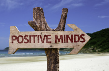 Positive Minds wooden sign with a beach on background