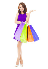 young woman holding shopping bags and hand gesture