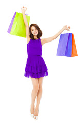 happy asian young woman raising shopping bags
