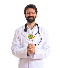 Doctor with lolly pop over white background