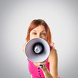 Redhead girl shouting with a megaphone over grey background