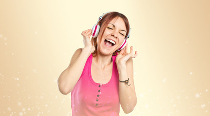 Young girl listening music over gloss background