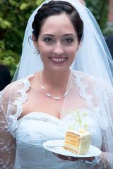 Braut serviert ein Stück Hochzeitstorte
