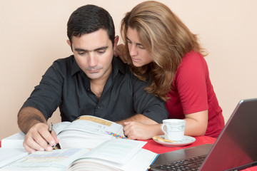 Hispanic man and woman studying at home