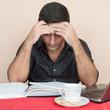 Tired hispanic man studying at home