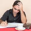 Stressed hispanic man studying at home