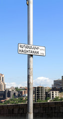 Signpost Haghtanak bridge on a background of city buildings