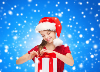 smiling girl in santa helper hat with gift box