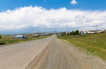 Asphalt road leading into the mountains through the village