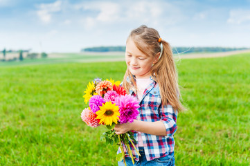 Outdoor portrait of adorable little girl playing with flowers