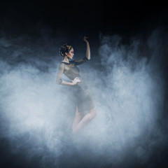 Young woman in a fashion dress posing in the fog
