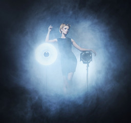 Young and emotional woman in a fashion dress on the smoke