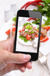 Hands taking photo vegetable salad with meat with smartphone