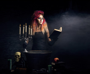 Beautiful witch making witchcraft on a Halloween background