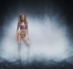 Fashion shoot of a young and sexy woman in the fog