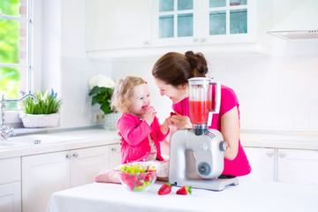 Young mother and daughter making fruit juice