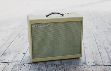 Yellow vintage guitar aplifier on wooden floor
