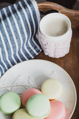 Hot cocoa in knitted cover and colorful macaroons on wooden tray