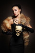 Young, rich and beautiful woman with a skull