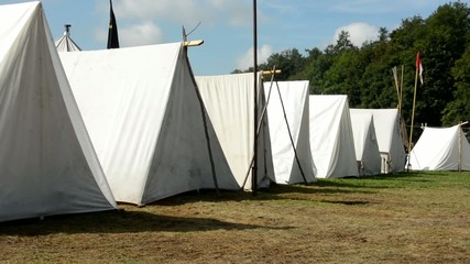 white block of tents - ground - forest (trees) - camp - sunny
