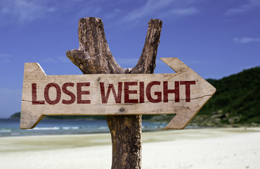 Lose Weight wooden sign with a beach on background