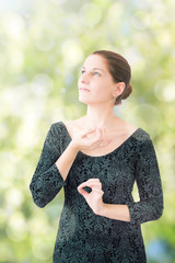 Young woman in relaxation pose on blurred natural background