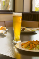 Tall Glass of Beer on Restaurant Table with Food