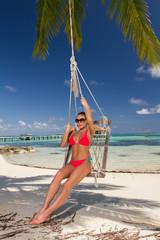 Sexy Woman in Red Bikini on Swing at the Beach