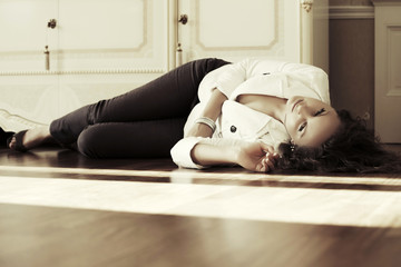 Sad beautiful fashion woman lying on the floor