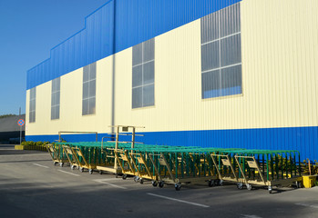 Cargo carts stand near the building of modern plant