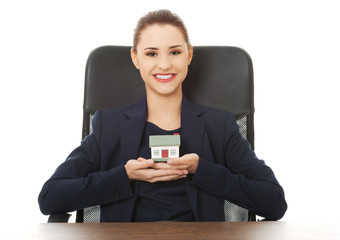 Happy real estate agent, holding a house model