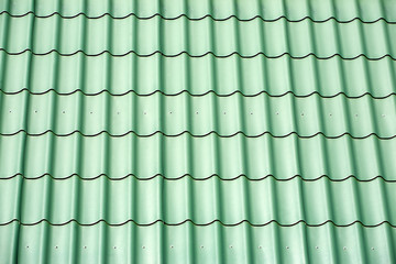 Green metal tile house roof as texture closeup