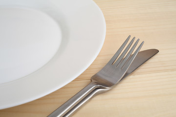 Empty plate with fork and knife on the wooden table