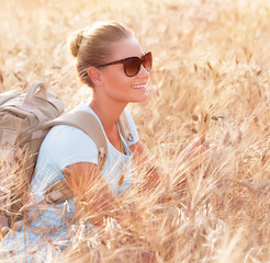 Happy traveler in wheat field