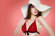 Beautiful fashion woman in white hat and red swimsuit posing