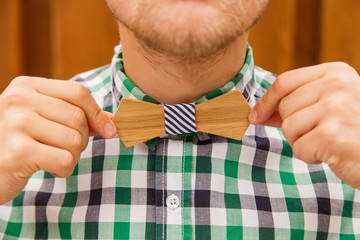 Casual young man correcting his retro wooden bow tie